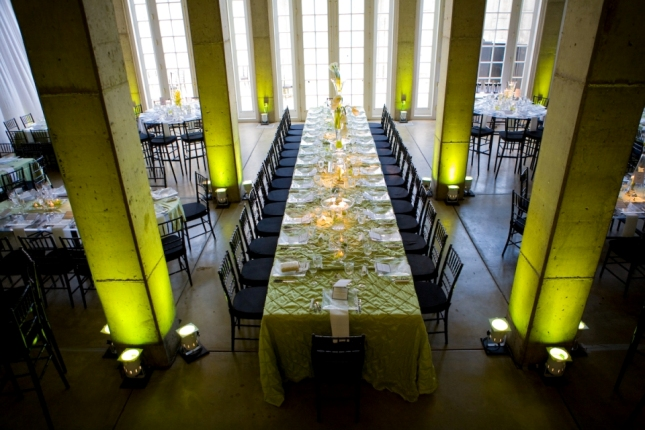 Head table for 25 guests with green linens and black chairs. Green uplighting on the columns.