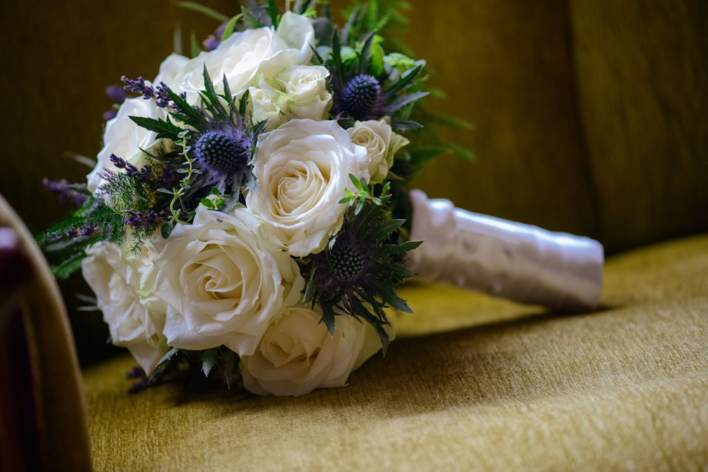 A white rose bridal bouquet with blue thistle
