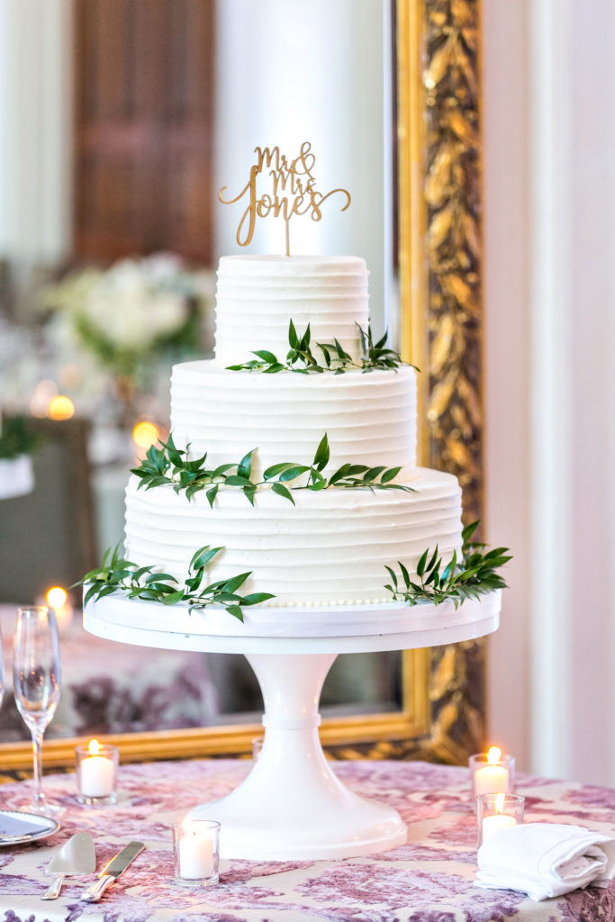 White buttercream wedding cake with greenery