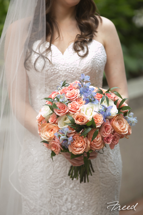 A peach bridal bouquet with blue accents