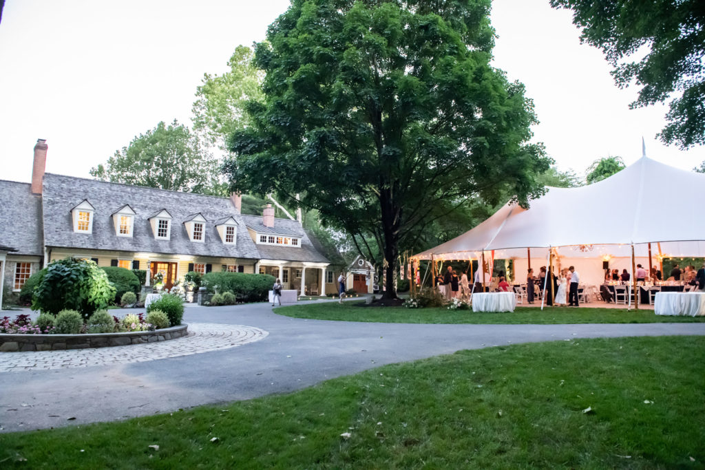 a private home in Maryland hosts a wedding. The sailcloth wedding reception tent is set up in the front yard, caddy corner to the house. coordinated by Bellwether Events